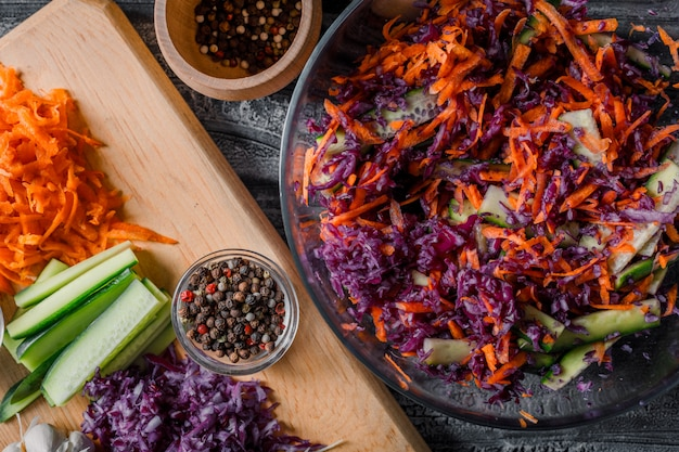 Vegetable salad in a bowl with with other chopped vegetables on a cutting board close-up on a dark wooden background