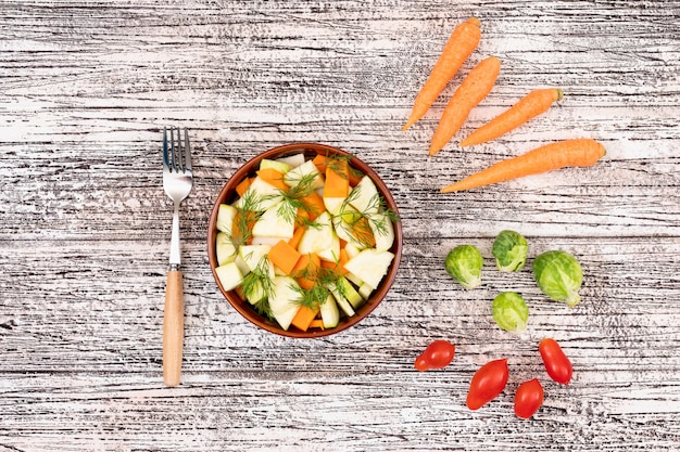 Vegetable salad in a ceramic bowl with fork carrot radish cherry tomato cabbage