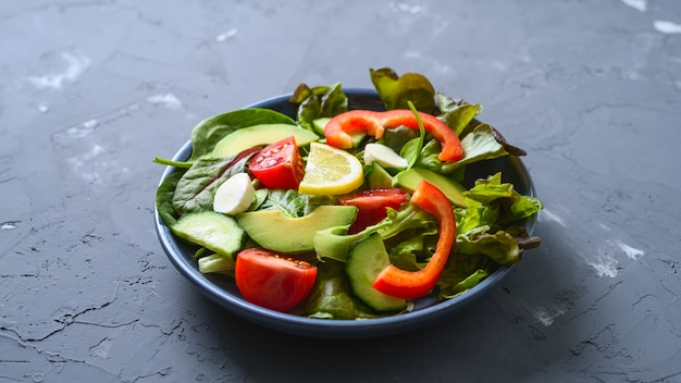 Vegetable salad of cucumbers, tomatoes, lettuce, avocado, bell pepper with mozzarella cheese