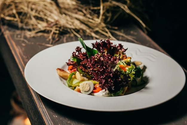 Vegetable salad in glass bowl on wooden table