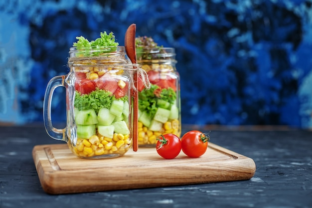 Vegetable salad in a glass jar and a spoon.