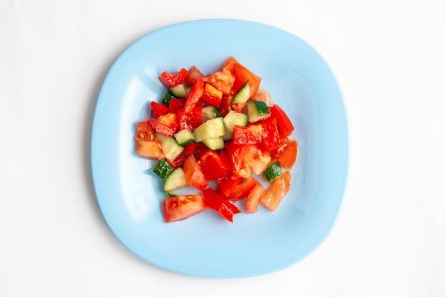 Овощной салат в голубой тарелке, изолированные на белом, вид сверху