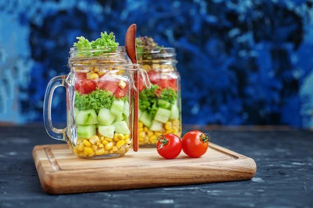 ガラス瓶とスプーンの野菜サラダ。