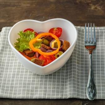 포크 옆에 체크 무늬 냅킨에 나무 테이블에 심장 모양 접시에 야채 샐러드. 정사각형 사진
