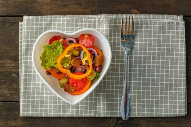 냅킨에 나무 테이블에 심장 모양 접시에 야채 샐러드.