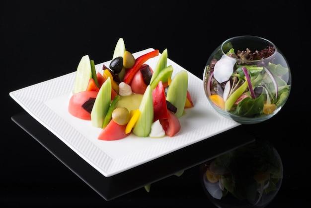 黒の背景、孤立した正方形のプレートの野菜サラダ