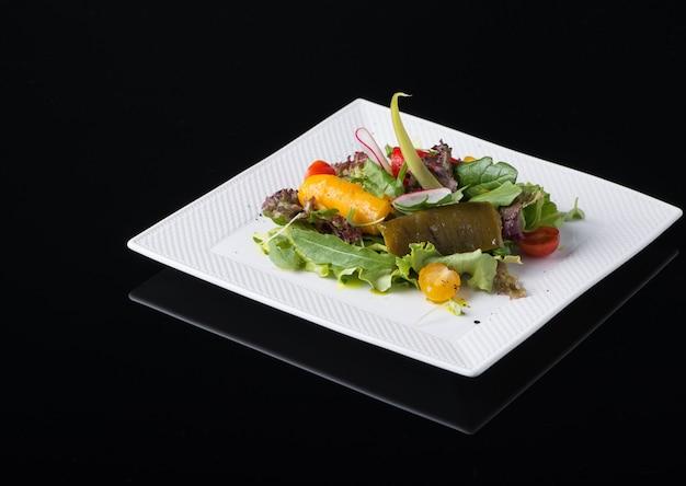 Овощной салат в квадратной тарелке на черном фоне, изолированные