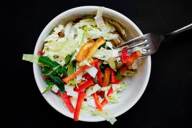 豆腐、トマト、キャベツ、にんじんの白いボウルに野菜サラダ