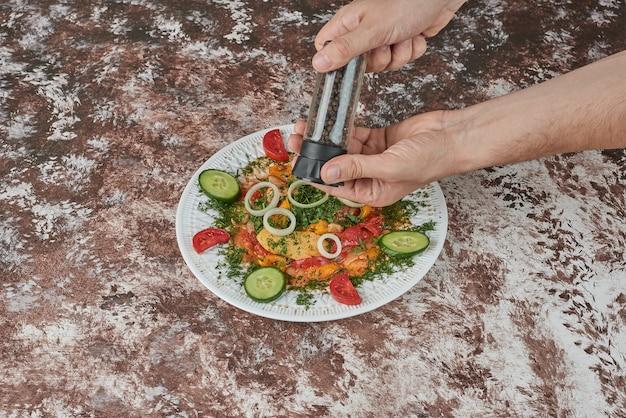色とりどりの食べ物が入った白いセラミックの盛り合わせの野菜サラダ。