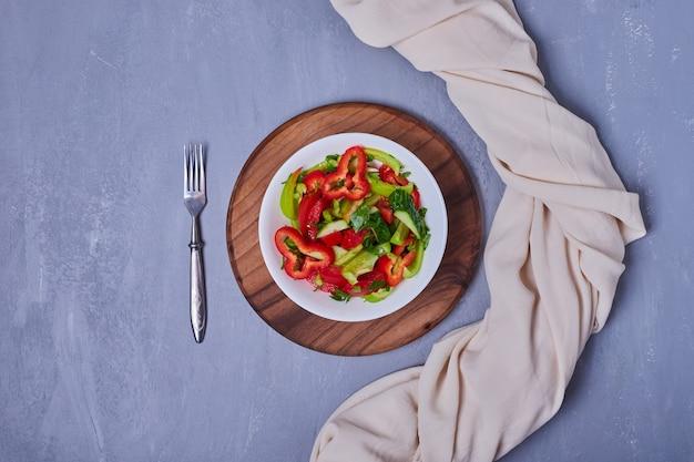 Овощной салат в белой тарелке на синем