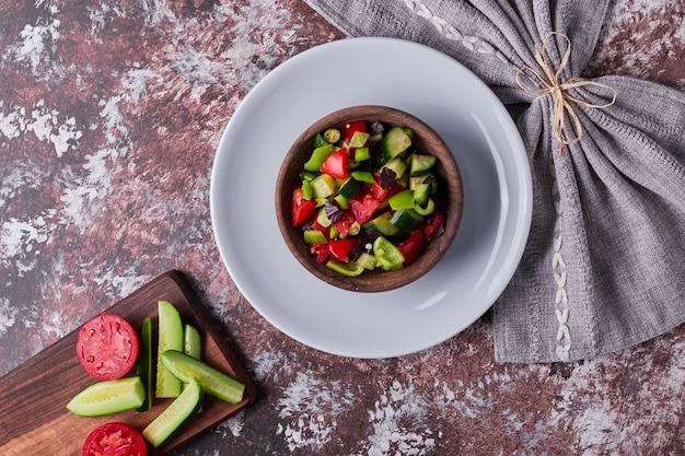 Овощной салат в деревянной чашке в белой тарелке.