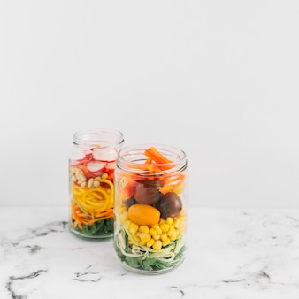 Vegetable salad in an open mason jar on marble top against white background