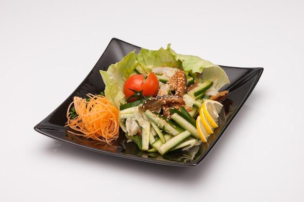 밝은 배경에 검은 사각형 접시에 야채 샐러드