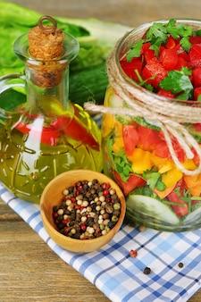 テーブル クロスの上の木製のテーブルの上のガラスの瓶の野菜サラダ