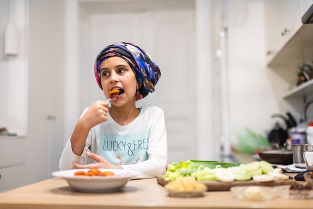 おかしな小さな男の形の野菜サラダ。子供は皿に切った野菜を食べる