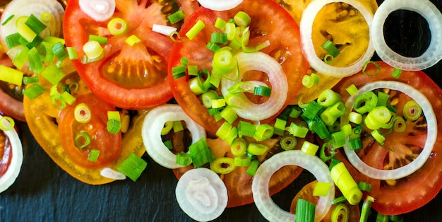 Vegetable salad ingredients - tomatoes, cucumbers, onion and greens