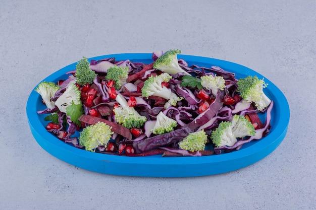 大理石の背景にザクロの仮種皮を混ぜた野菜サラダ。