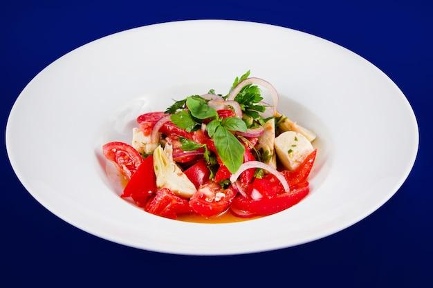 파란색 배경에 흰색 접시에 토마토, 고추, 양인데, 양파의 야채 샐러드.