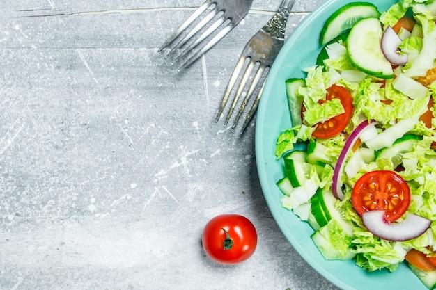野菜サラダ。きゅうり、トマト、赤玉ねぎのスパイスとオリーブオイルのサラダ。素朴な背景に。