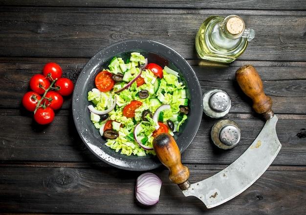 野菜サラダ。きゅうり、トマト、赤玉ねぎのスパイスとオリーブオイルのサラダ。木製のテーブルの上。