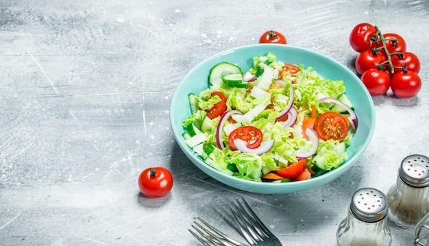 野菜サラダ。きゅうり、トマト、赤玉ねぎのサラダ、素朴なテーブルにスパイスとオリーブオイルを添えて。