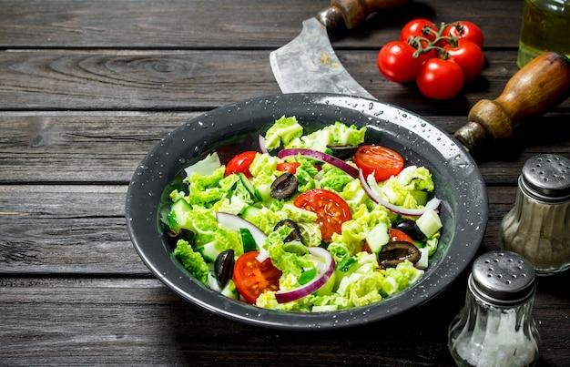 野菜サラダ。きゅうり、トマト、赤玉ねぎのサラダ、スパイスとオリーブオイルの木製テーブル。