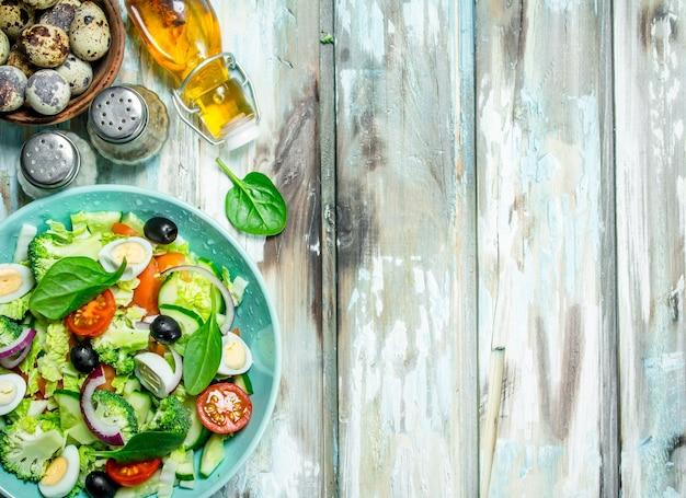 Овощной салат. салат из помидоров, огурцов и перепелиных яиц с оливковым маслом на деревенском столе.
