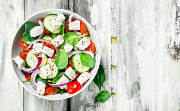 Овощной салат. салат с овощами, сыром и оливковым маслом. на деревенском фоне.
