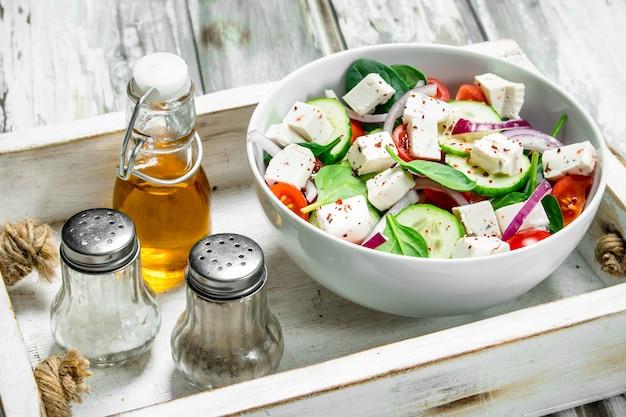 Овощной салат. салат с овощами, сыром и оливковым маслом. на деревенском столе.