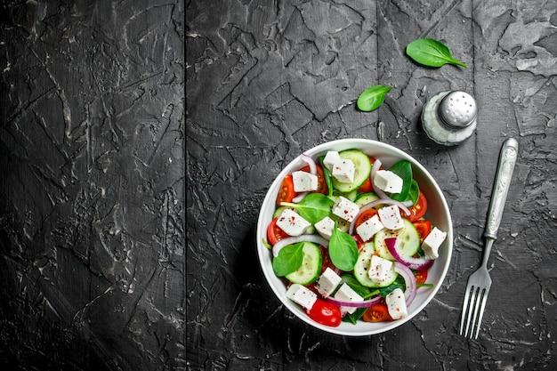 Овощной салат. салат с овощами, сыром и оливковым маслом. на черном деревенском фоне.