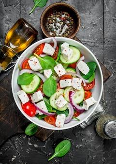 Овощной салат. салат с овощами, сыром и оливковым маслом. на черном деревенском столе.