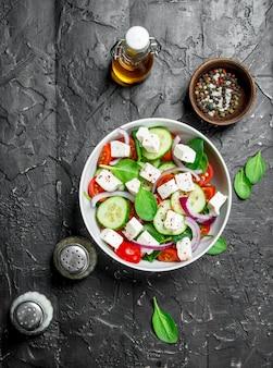Овощной салат. салат с овощами, сыром и оливковым маслом на деревенском столе.