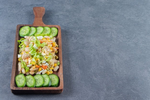 Vegetable salad and sliced cucumbers on a board, on the marble background.
