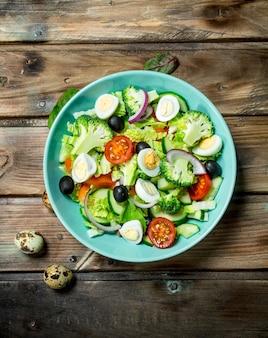 Овощной салат. салат из помидоров, огурцов и перепелиных яиц с оливковым маслом и базиликом. на деревянном.