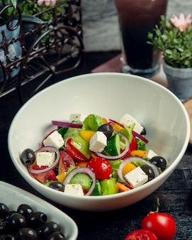 Vegetable salad topped with olives and cheese