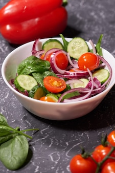 Vegetable salad in a white plate on a gray background