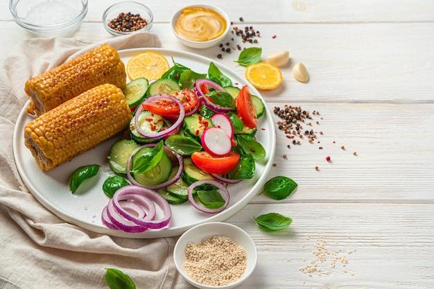 明るい壁にバジルとゴマとコーンを添えた野菜サラダ。健康食品。
