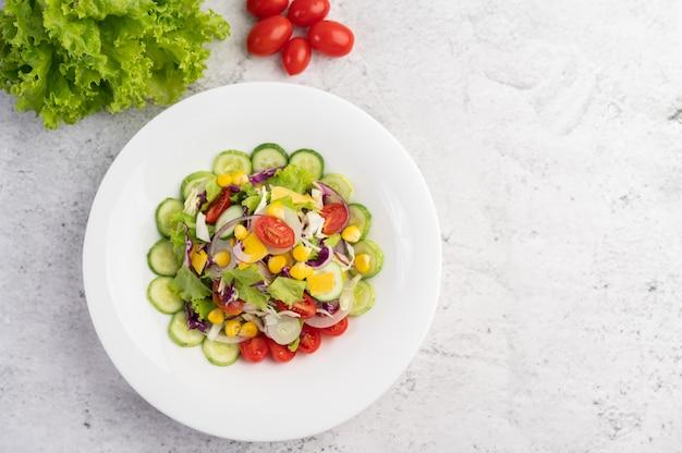 Овощной салат с вареными яйцами в белом блюде.