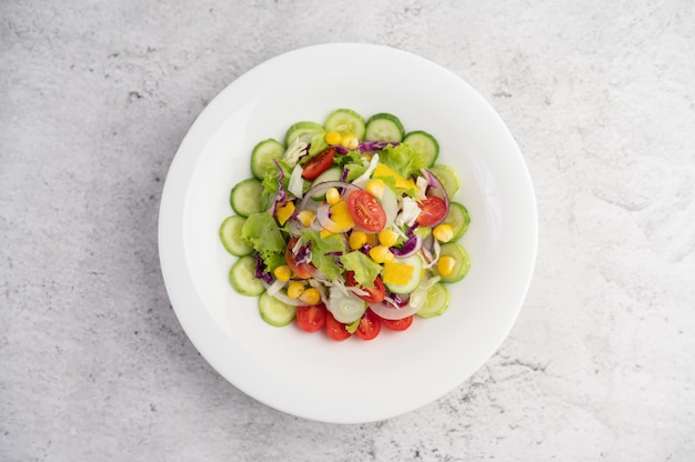Vegetable salad with boiled eggs in a white dish.