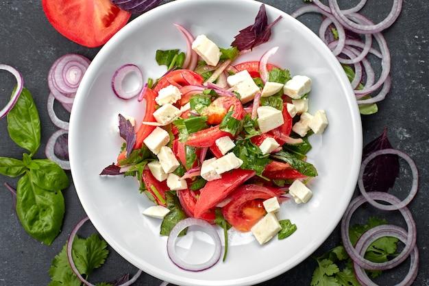흰색 접시에 치즈와 야채 샐러드