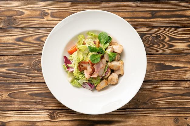 Овощной салат с курицей и беконом в белой керамической тарелке