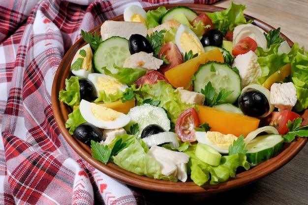 Овощной салат с курицей и яйцами, оливками в листьях салата горизонтальный снимок крупным планом