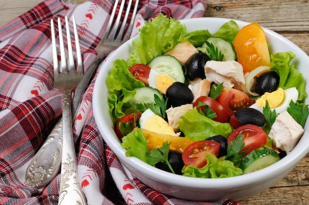 レタスの葉に鶏肉と卵のオリーブを添えた野菜サラダ横ショット