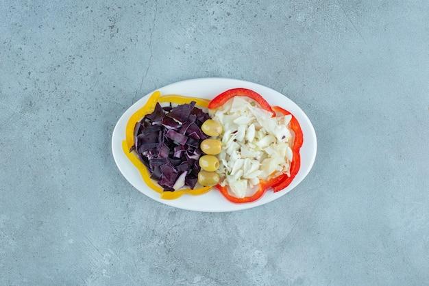 Овощной салат с нарезанной и измельченной цветной капустой, капустой и другими ингредиентами.