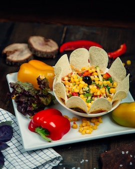 Vegetable salad with corn seeds, color bell pepper,  herbs and chips.