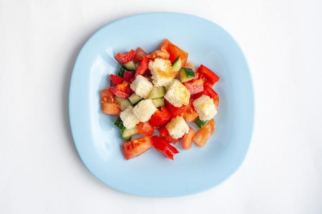 Овощной салат с крекерами в синей тарелке, изолированные на белом, вид сверху