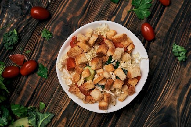 Овощной салат с крекерами на деревянном столе
