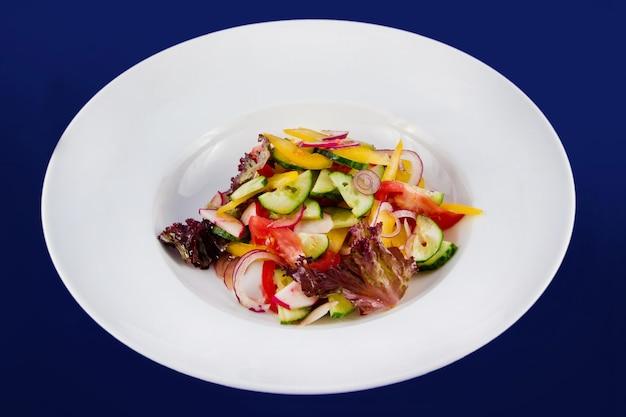 오이, 토마토, 무, 무, 피망, 양파, 양상추를 곁들인 야채 샐러드. 파란색 배경에 흰색 접시에 평면 위치 최고보기.