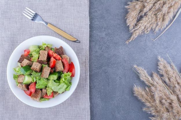 Овощной салат с сушеной корочкой на скатерти рядом с сушеными стеблями иглы на мраморной поверхности