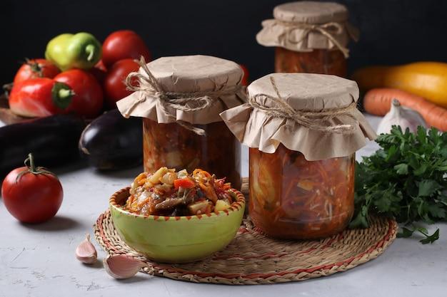 Овощной салат с баклажанами, морковью, перцем, чесноком, помидорами в миске и стеклянных банках на темноте